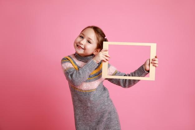 ピンクの背景にモックアップの空白のフレームを保持している小さな笑顔の女の子の肖像画。