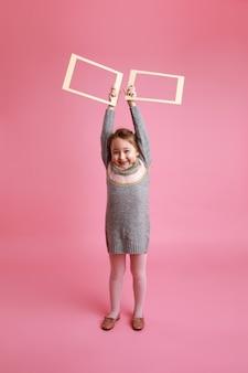 ピンクの背景にモックアップのための高い2つの空白のフレームを保持している小さな笑顔の女の子の肖像画