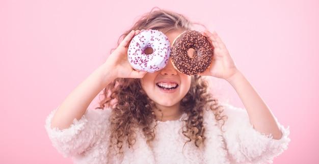 Портрет маленькой улыбающейся девушки с пончиками