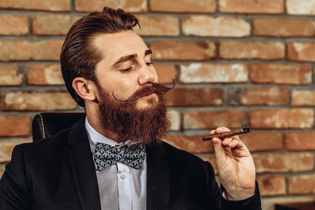 レンガの壁の背景に茶色の葉巻を吸う口ひげとあごひげを持つ素敵な大人の残忍な男の肖像画。葉巻のコンセプト