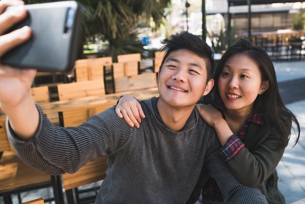 楽しい時間を過ごし、コーヒーショップで携帯電話で自分撮りをしている素敵なアジアのカップルの肖像画。