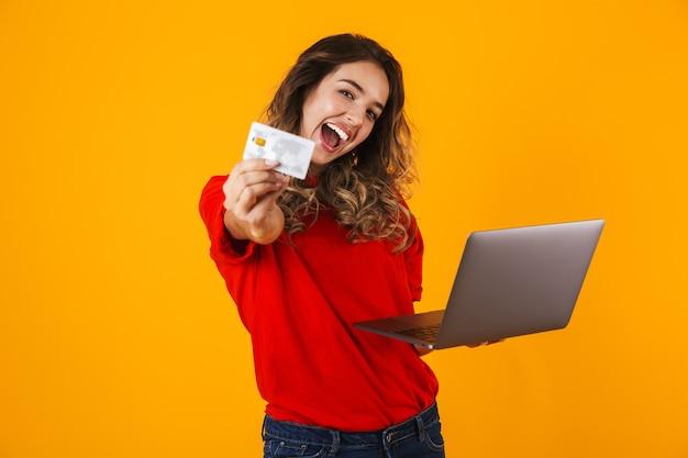 Портрет прекрасной веселой молодой женщины, стоящей изолированно над желтой стеной, работающей на портативном компьютере и показывающей кредитную карту