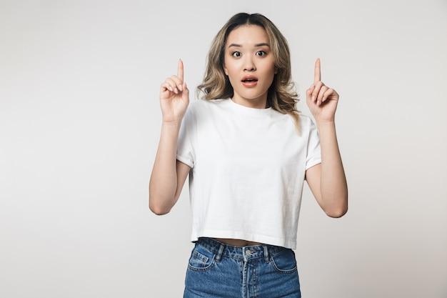 コピースペースを指して、白い壁の上に孤立して立っている素敵な興奮した若いアジアの女性の肖像画