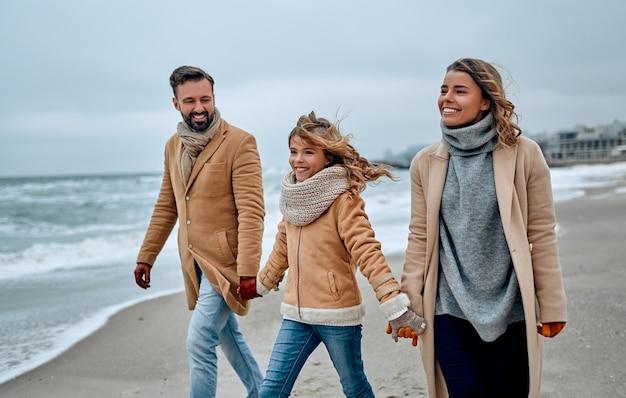 冬のビーチで手をつないで歩いている素敵な家族の肖像画。