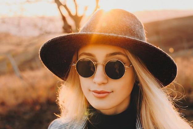 彼女の休暇時間の日の出に対して夕方に旅行中に目をそらしている帽子とレトロなサングラスを身に着けている素敵な女性の肖像画。