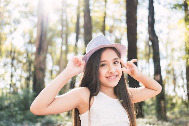 幸せに笑っている素敵な女の子の肖像画-屋外で帽子をかぶっている美しい長髪の女の子。