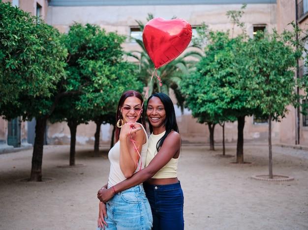 거리에서 야외에서 빨간 하트 모양의 풍선을 들고 포옹하는 사랑스러운 레즈비언 커플의 초상화. lgbt 개념입니다.