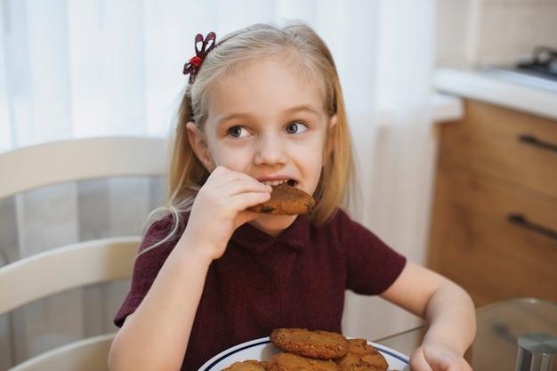 キッチンで朝にクッキーを食べる素敵な小さなブロンドの女の子の肖像画。
