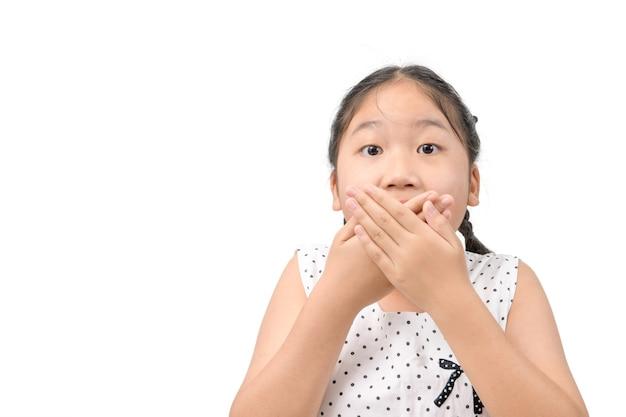 白い背景で隔離の両手で彼女の口を覆う、驚きと衝撃の概念の素敵な少女の肖像画