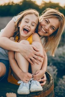 닫힌 눈으로 웃고 사랑스러운 어린 소녀의 초상화는 그녀의 어머니에 의해 포용되는 동안 웃고 일몰에 반대합니다.