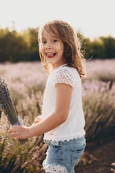 Портрет прекрасной маленькой девочки, смотрящей в камеру, развлекающейся, показывая язык, держащий букет цветов в поле цветов на закате.