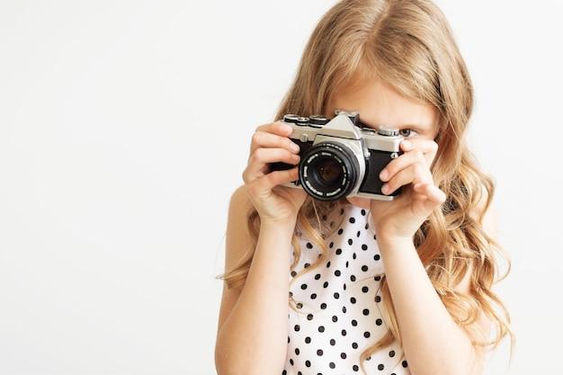 흰색 배경에 대해 오래된 slr 필름 카메라로 사랑스러운 어린 소녀의 초상화