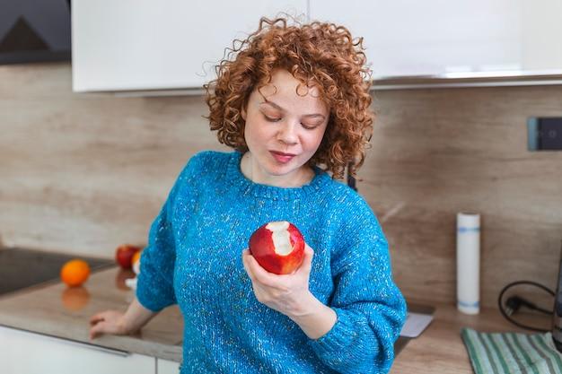 그녀의 부엌에서 사과 물고 사랑스러운 웃는 예쁜 여자의 초상화. 그녀의 빨간 유기농 사과 과일을 즐기는 젊은 여자. 과일과 함께 매일 비타민 섭취, 다이어트 및 건강식