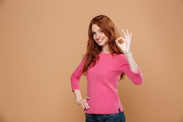 확인 제스처를 만드는 사랑스러운 웃는 빨간 머리 여자의 초상화