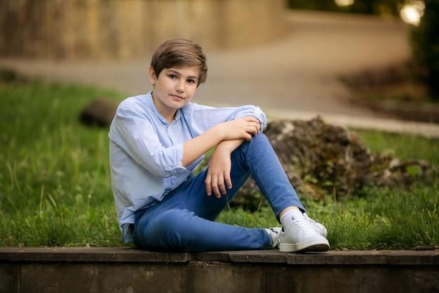 Портрет прекрасного подростка мальчика 10 лет в парке летом