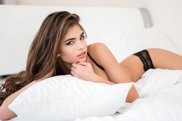 ベッドに横になっていると、カメラ目線のランジェリーの素敵な女性の肖像画