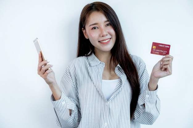 Портрет милой молодой азиатской красивой женщины с длинными волосами, держащей красную кредитную карту и смартфон, сверкающими глазами в камеру