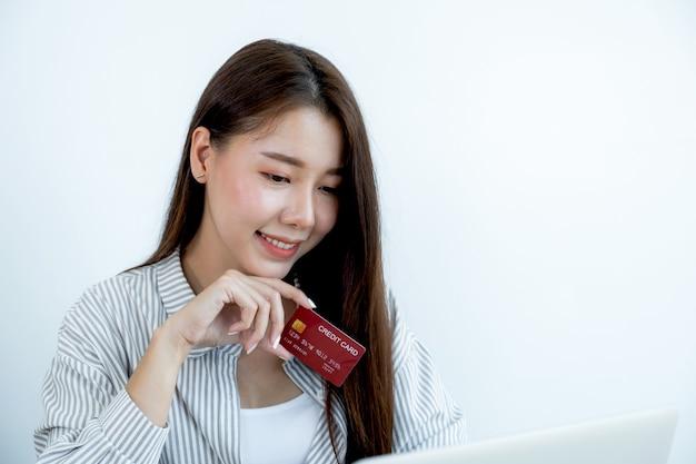 赤いクレジットカードを保持している長い髪の素敵な若いアジアの美しい女性の肖像画