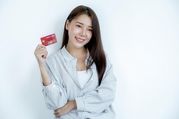 Портрет милой молодой азиатской красивой женщины с длинными волосами, держащей красную кредитную карту