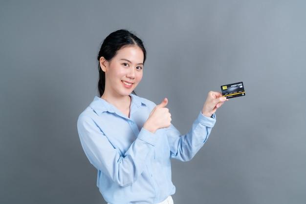 灰色の表面にクレジットカードを示す青いシャツの素敵な若いアジアの女性の肖像画