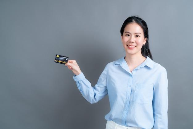 Портрет милой молодой азиатской женщины в голубой рубашке, показывающей кредитную карту с копией пространства на сером фоне