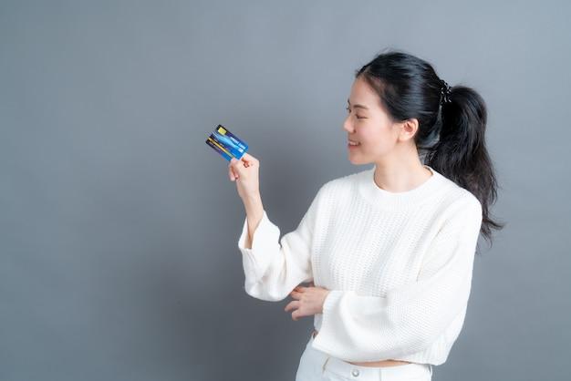 Портрет милой молодой азиатской женщины в свитере, показывающей кредитную карту с копией пространства на сером фоне
