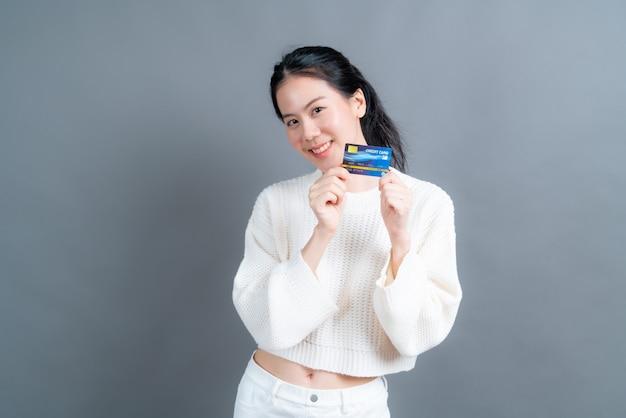 Портрет милой молодой азиатской женщины в свитере, показывающей кредитную карту с копией пространства