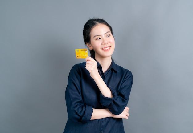 灰色の表面にコピースペースでクレジットカードを示す素敵な若いアジアの女性の肖像画
