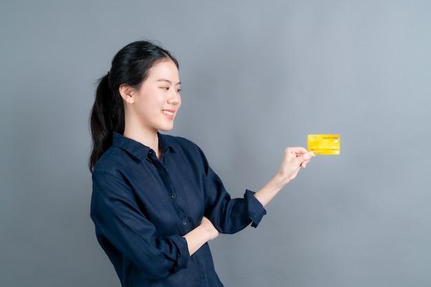 Портрет милой молодой азиатской женщины, показывающей кредитную карту с копией пространства