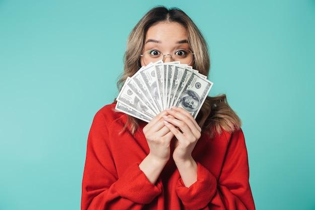 青い壁の上に孤立して立って、お金の紙幣を示す素敵な若いアジアの女性の肖像画