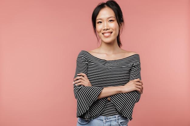 팔짱을 끼고 분홍색 벽 위에 고립된 채 서 있는 사랑스러운 젊은 아시아 여성의 초상화