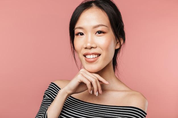 분홍색 벽 위에 고립된 채 포즈를 취하고 있는 사랑스러운 젊은 아시아 여성의 초상화