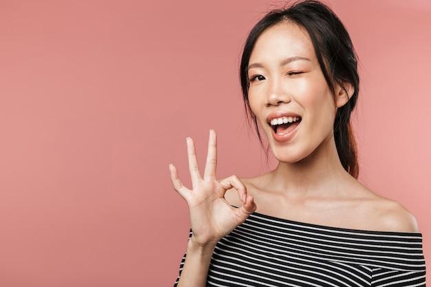 분홍색 벽 위에 고립된 채 서 있는 사랑스러운 젊은 아시아 여성의 초상화