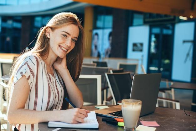 야외 커피 숍에서 커피를 마시는 동안 노트북에 쓰는 사랑스러운 젊은 비즈니스 여자의 초상화. 빨간 머리 여성 미소.