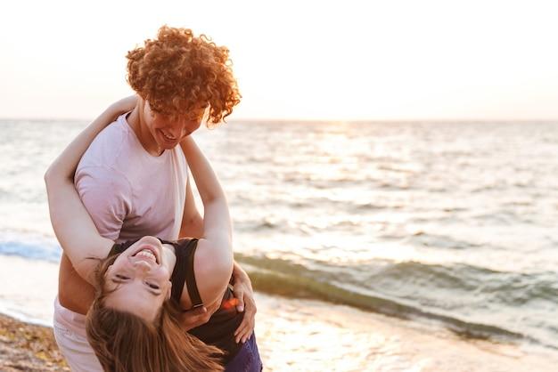 Портрет прекрасной молодой пары, обнимающейся на пляже, весело