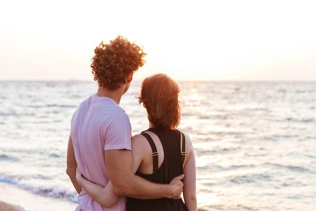 Портрет прекрасной молодой пары, обнимающейся на пляже, глядя на восход солнца
