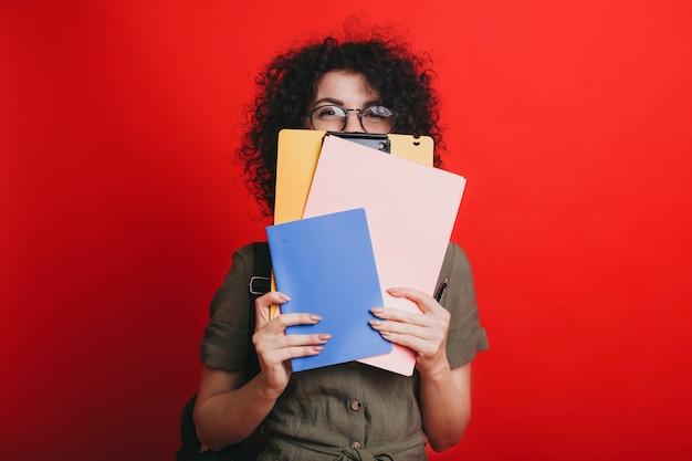 빨간 스튜디오 배경 위에 고립 된 그녀의 공부 책으로 그녀의 얼굴을 숨기고 사랑스러운 젊은 곱슬 여성 학생의 초상화.