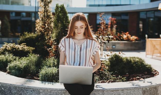 수업 후 그녀의 노트북을보고 사랑스러운 어린 소녀의 초상화. 그녀의 노트북 야외에서 숙제를 하 고 젊은 여성 학생.