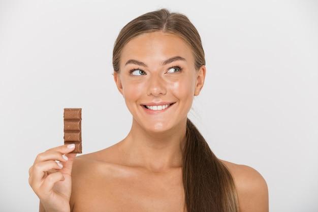 孤立したチョコレートの部分を保持している素敵な若いトップレスの女性の肖像画
