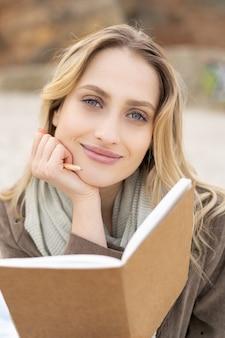 해변에 앉아 약간의 미소로 열린 노트북을 들고 사랑스러운 젊은 여자의 초상화