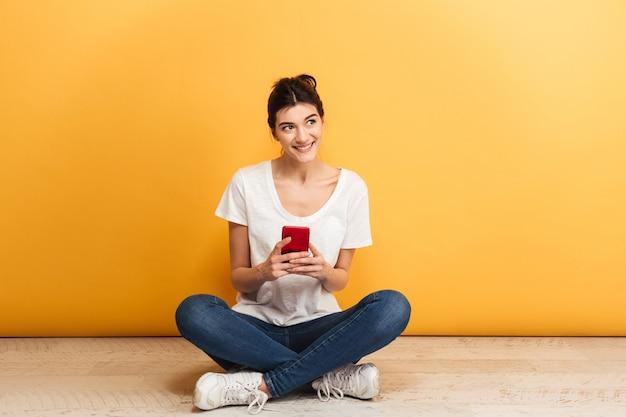 携帯電話を保持している素敵な若い女性の肖像画