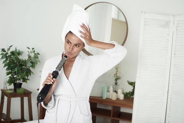 ヘアドライヤーをマイクとして使用して、タオルで髪を包んだ素敵な若い女性の肖像画。家でリラックスして楽しんでください。