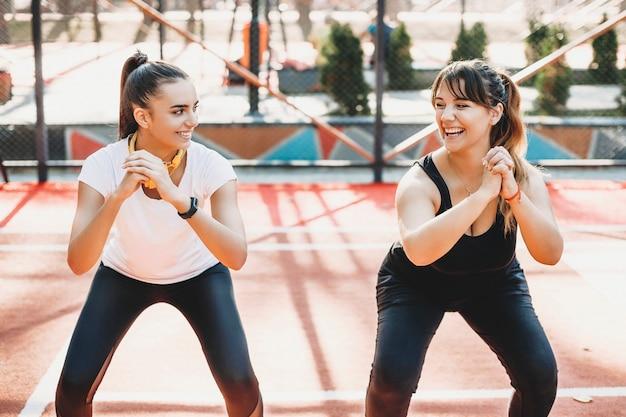 Портрет милой молодой женщины, смеющейся, делая упражнения для похудения со своей девушкой в спортивном парке.