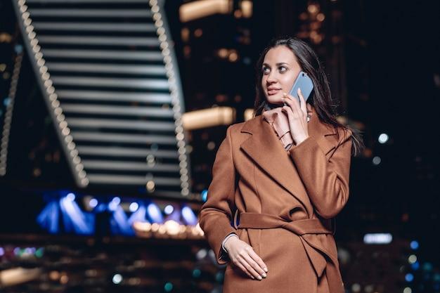 コートを着て、モスクワの夜の明かりを背景に電話で話している素敵な若い働く女性の肖像画。