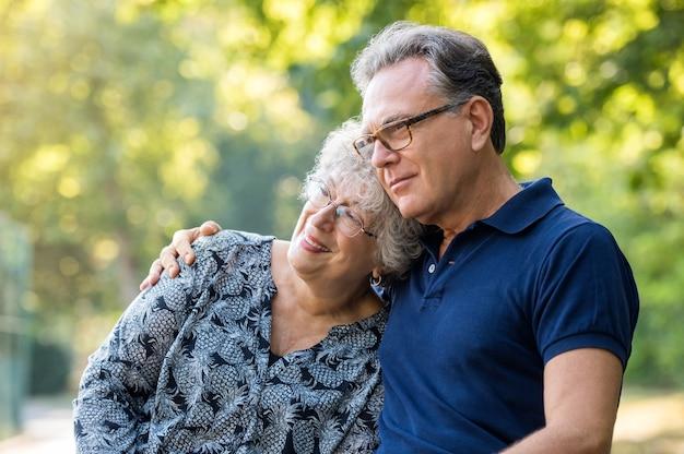 公園で抱きしめる愛情のある成熟したカップルの肖像画
