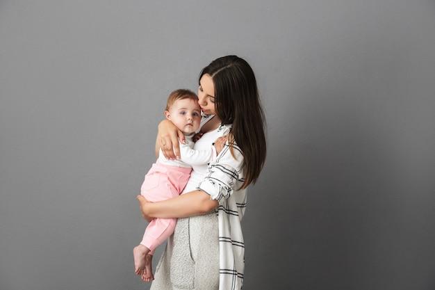 彼女の小さな赤ちゃんを保持している愛情のある若い母親の肖像画