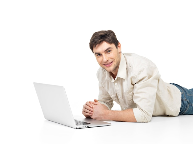 白で隔離のラップトップで嘘をついて成功した幸せな男の肖像画。
