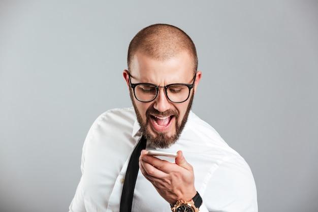 Портрет сумасшедшего бизнесмена кричать на мобильный телефон