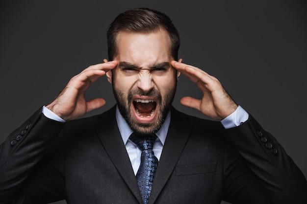 孤立した、頭痛を持っているスーツを着ている狂ったハンサムなビジネスマンの肖像画
