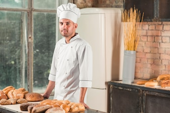 Portrait of a male baker with various baked breads